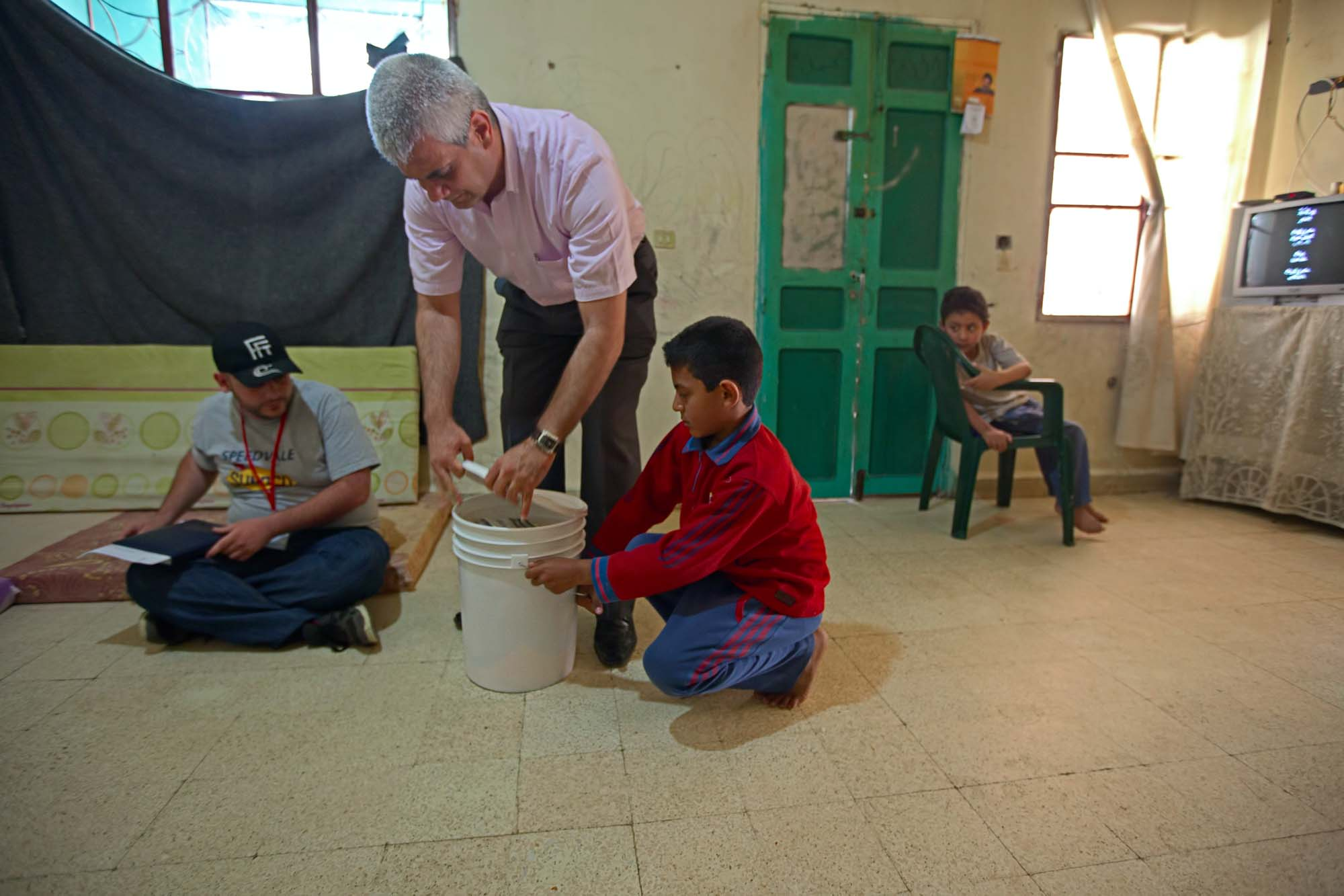 A man opens the lid of a white plastic bucket with assistance from a boy. A man and another boy watch.