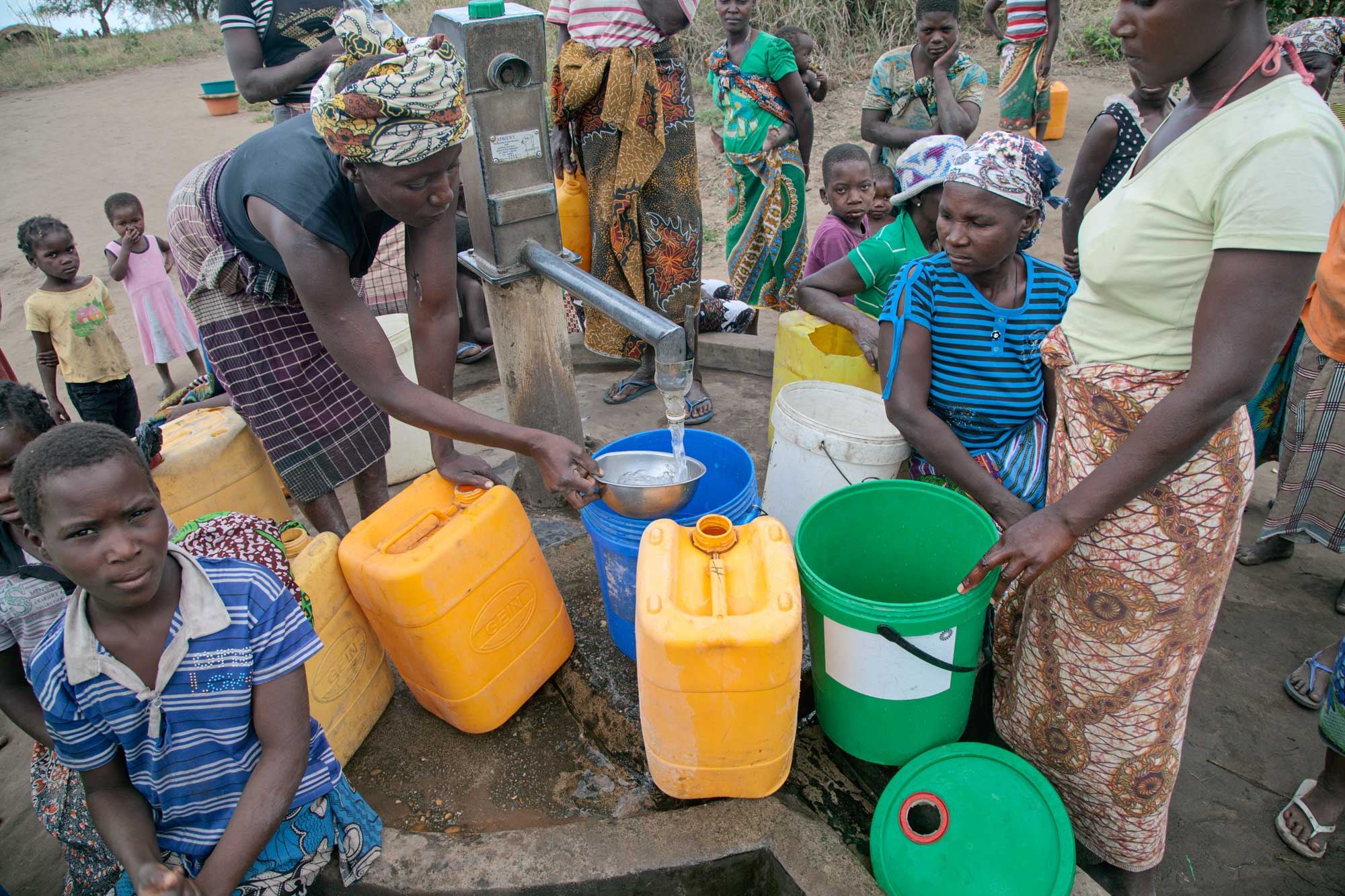 Women and children fill containers from at a capped well.