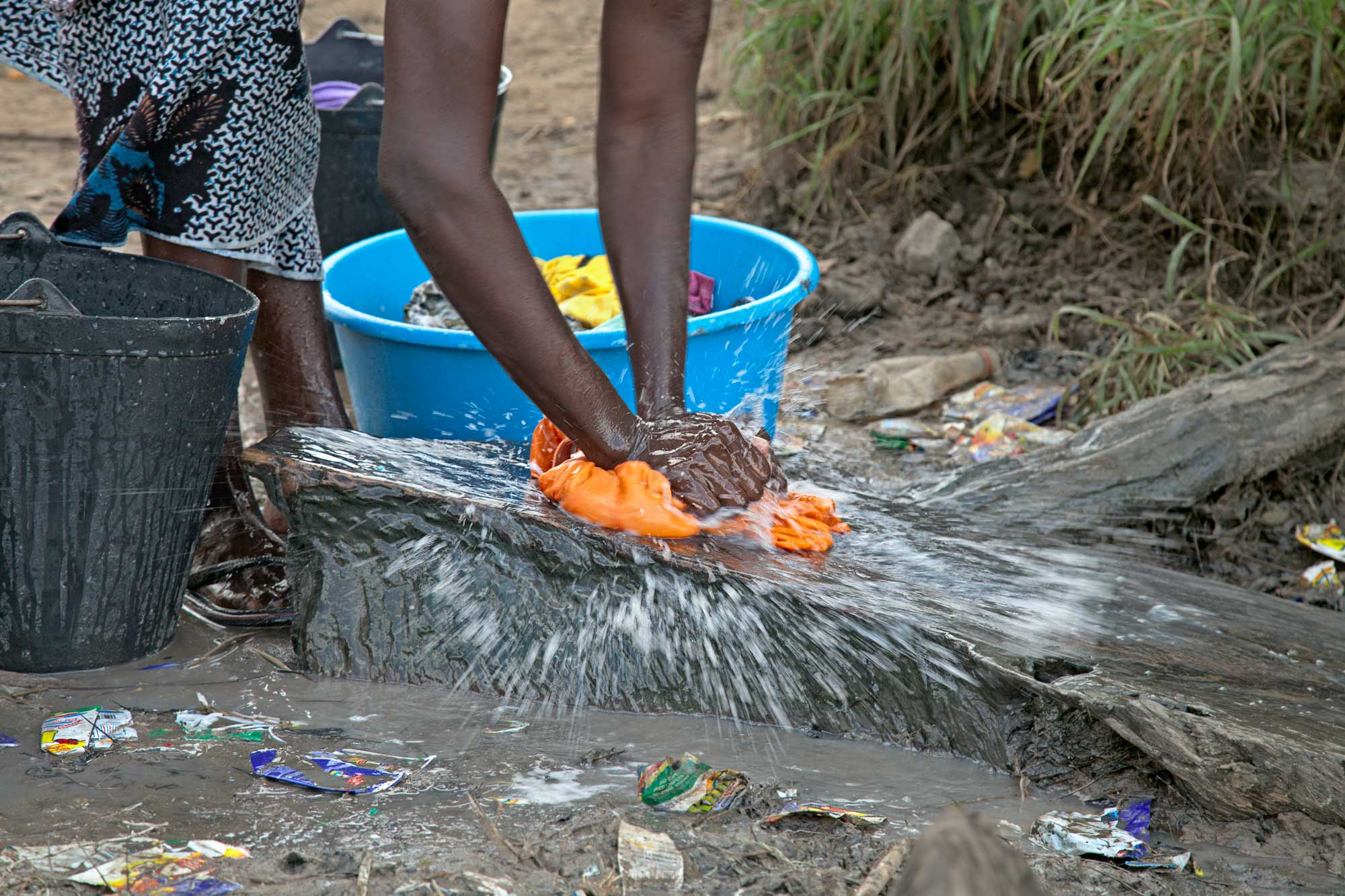 Clothing is slapped against a large stone as a women washes clothes.