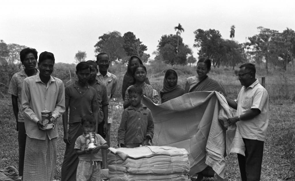 """<span class=""""photo-caption"""">In 1972, refugees returning to their homes near Birisiri, Bangladesh, received the gift of MCC blankets and canned chicken, thanks to a distribution by the Bangladesh Council of Churches. The supplies - a few bales and cartons at a time - were sent from Mymensingh over a rough road, on two ferries and over broken bridges to the Garo Baptist Center. Pictured are recipients and Hiten Areng (far right), general secretary of the Garo Baptist Union.</span><span class=""""photo-credit"""">MCC Photo/John Wieler</span>"""