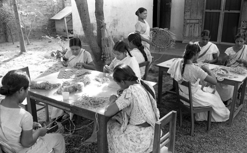 """<span class=""""photo-caption"""">Opportunity for families in Bangladesh expanded to include a MCC job creation program that supported initiatives to create and sell handicrafts. In this 1974 photo, women are developing products from jute fiberwhich can be twisted into a tough coarse yarn and woven into items such as doilies, belts, hats, and rugs. Today MCC continues to support job creation activities in Bangladesh, and many enterprises are now financially independent and sell to international fair trade organizations.</span><span class=""""photo-credit"""">MCC Photo/Burton Buller</span>"""