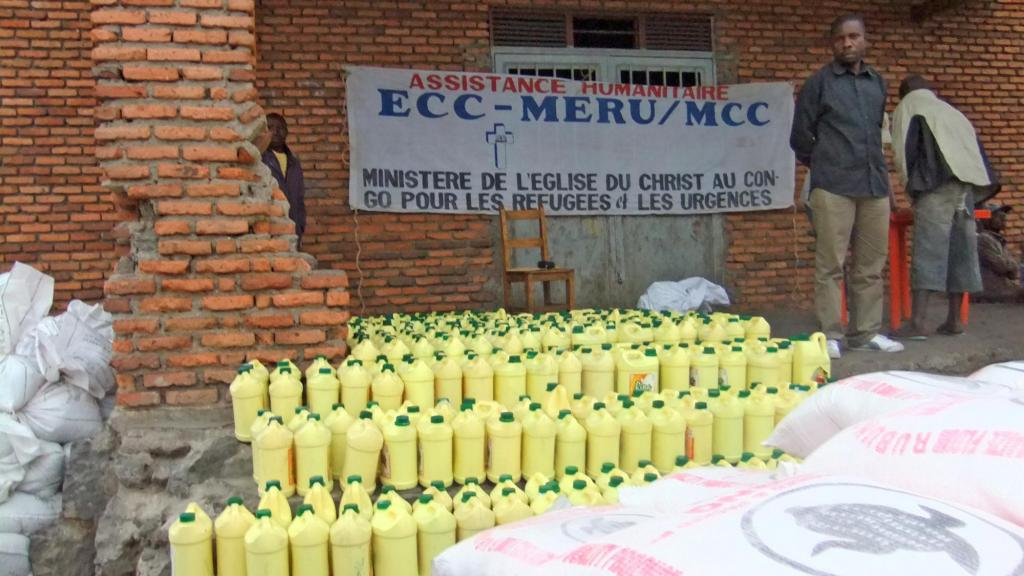 """<span class=""""photo-caption""""><span>Mitterand Aoci, who works for the Church of Christ of Congo's Ministry of Refugees and Emergencies (ECC-MERU) in North Kivu, eastern Congo, stands beside cooking oil which is part of an MCC-funded food distribution.</span></span><span class=""""photo-credit"""">Photo by Michael Sharp</span>"""