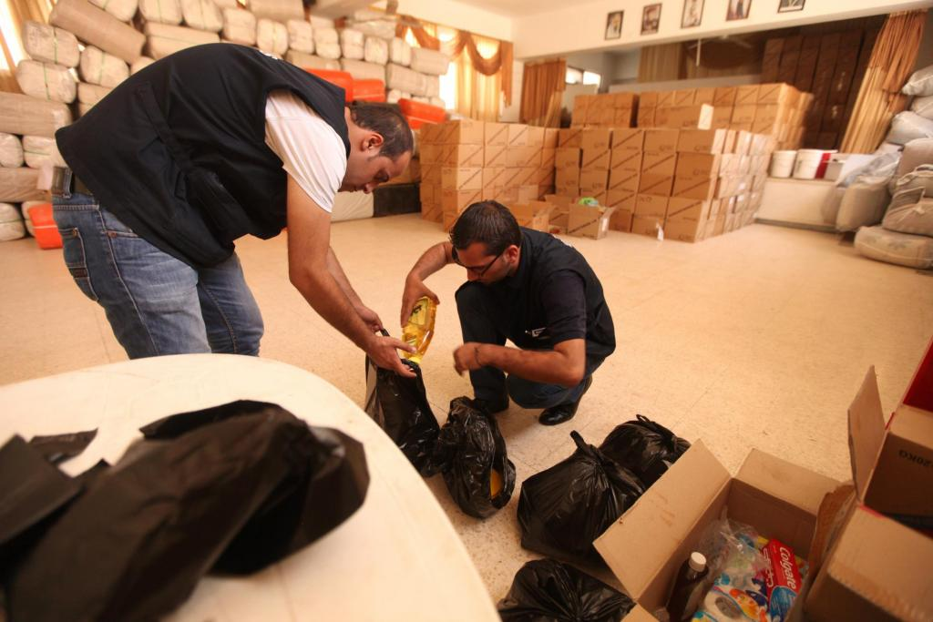 """<span class=""""photo-caption""""><span>MCC hygiene kits, relief kits and comforters meet basic needs of Syrian refugees who have fled to Jordan. From left, Wajdi Sahawne, a caseworker for MCC partner Caritas Jordan and Hussam Nasrawne, a supervisor for a Caritas Jordan center in Mafraq, assemble supplies for refugees. Behind them are bales of comforters and boxes of hygiene kits.</span></span><span class=""""photo-credit"""">Photo by Silas Crews</span>"""