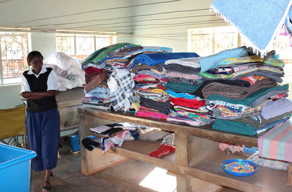 """<span class=""""photo-caption""""><span>Lirance Haadinke, a nurse at Brethren in Christ Macha Mission Hospital, stands by a table of MCC comforters. The hospital, located in rural Choma district in southern Zambia, received 100 AIDS caregiver kits, some extra linens and mattress covers, as well as 350 comforters in this 2012 shipment.</span></span><span class=""""photo-credit"""">Photo by Donna Martens</span>"""