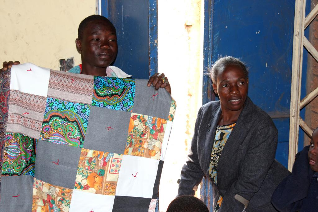"""<span class=""""photo-caption""""><span>Sephania Sitta, a student at the School for Disabled Children in Lusaka, Zambia, which serves students from about 5 to 16 years old, shows his MCC comforter, while teacher Hellen Kankasela Chikalamu looks on. Each student received an MCC comforter and school kit. During several visits to the school, which is part of MCC-funded peace club activities, MCC workers noticed the dedication of the teachers who are themselves living with disabilities.</span></span><span class=""""photo-credit"""">Photo by Donna Martens</span>"""