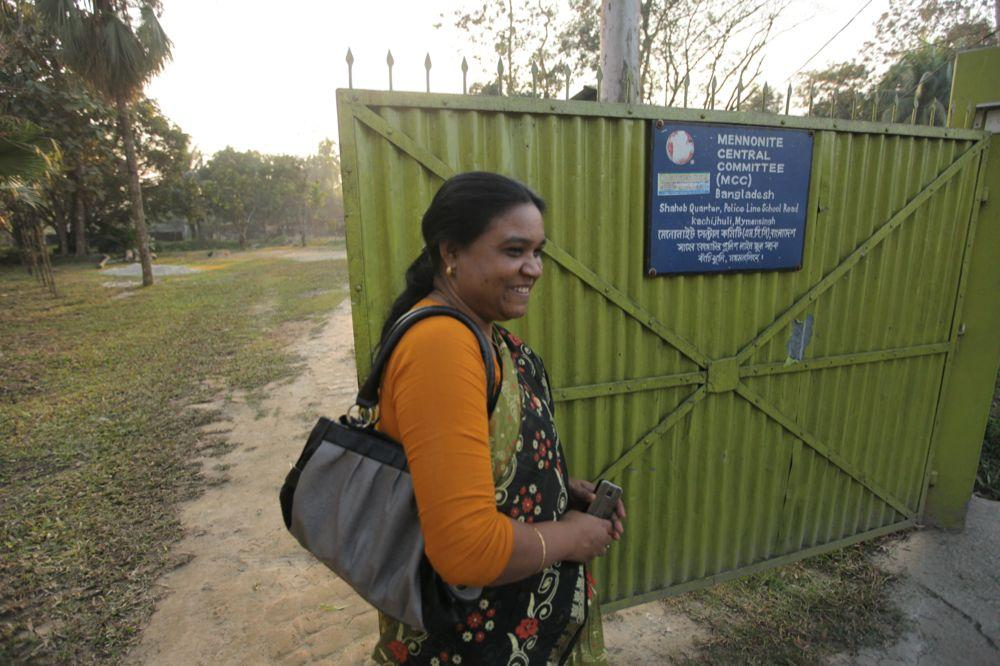 """<span class=""""photo-caption"""">Ferdoushi Howlader, MCC Bangladesh job creation project supervisor, walks past the entrance to MCC's research and design facility in Mymensingh, Bangladesh. MCC also created a fiber research center to develop new materials and techniques for processing pineapple and banana leaf fibers used in creating thread, yarn and fabrics.</span><span class=""""photo-credit"""">MCC Photo/Silas Crews</span>"""
