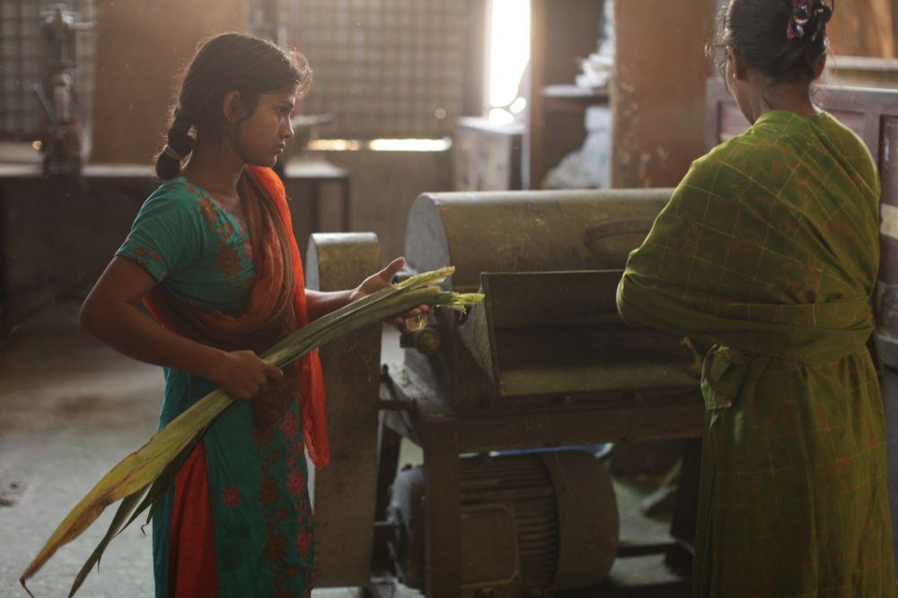 """<span class=""""photo-caption"""">Nazma Begum, left, and Beauty Begum operate a machine that crushes leaves and separates the fiber used to make thread.</span><span class=""""photo-credit"""">MCC Photo/Silas Crews</span>"""