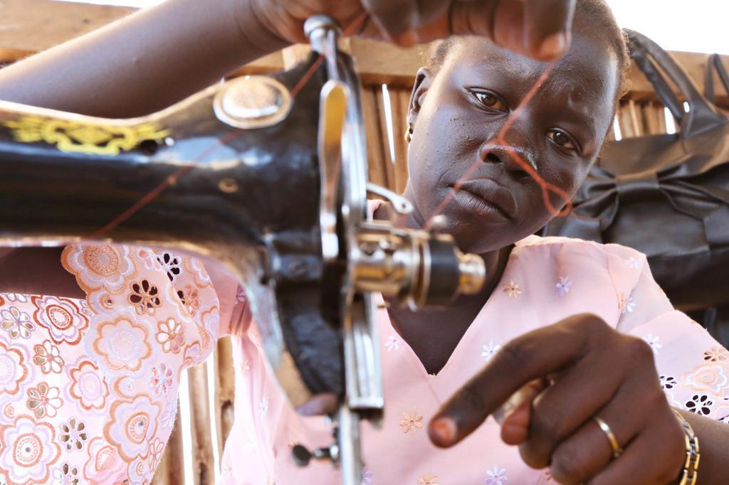 "<span class=""photo-caption""><span>Teresa </span>Festo<span> threads her sewing machine. Through the program, women learn sewing, life skills and small business management.</span><br /></span><span class=""photo-credit"">MCC Photo/Nina Linton</span>"