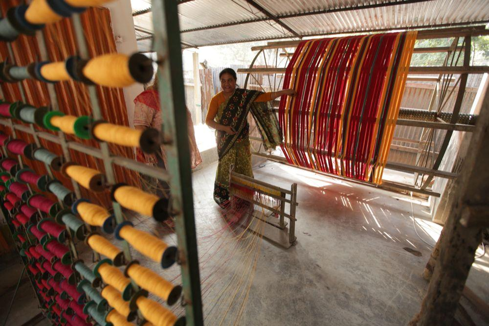 """<span class=""""photo-caption"""">Ferdoushi Howlader shows thread that has been dyed and rolled onto spools. The threads are then used by weavers to create fabric that is later made into clothing.</span><span class=""""photo-credit"""">MCC Photo/Silas Crews</span>"""