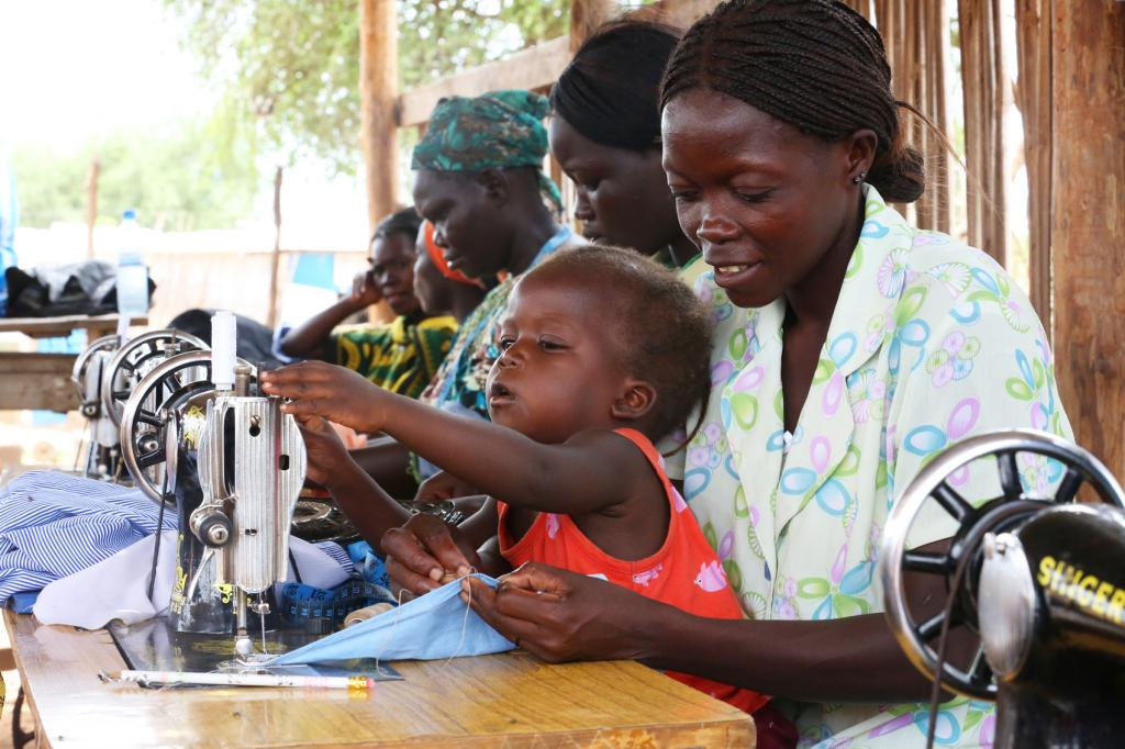 """<span class=""""photo-caption"""">Staying close to their mothers, children become familiar with sewing machines and the sights and sounds of a sewing class. Ester Keji, 2, explores the mechanical aspects of a sewing machine while her mother Jerisa Muro is busy with her hand stitching.</span><span class=""""photo-credit"""">MCC Photo/Nina Linton</span>"""