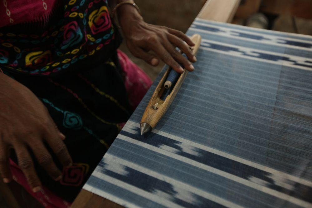 """<span class=""""photo-caption"""">A worker adjusts a spool of indigo dyed thread as she works at her loom to create a test fabric. This type of fabric is often used for a thin shawl or head covering.</span><span class=""""photo-credit"""">MCC Photo/Silas Crews</span>"""