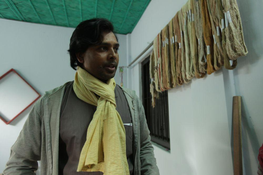 """<span class=""""photo-caption"""">MCC Bangladesh Designer Abir Das displays a scarf made from exotic fiber created at the research and design facility. Designers play an important role in choosing patterns, colors and style of new products.</span><span class=""""photo-credit"""">MCC Photo/Silas Crews</span>"""