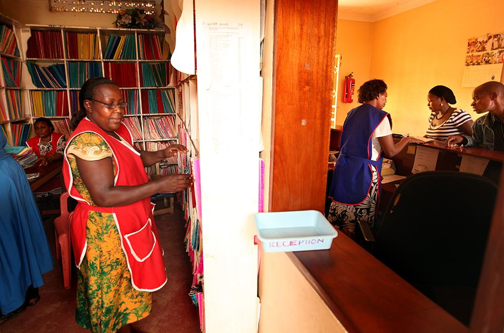 """<span class=""""photo-caption"""">Regina Nuwagaba, a member of the clinical support staff at the Mengo Hospital Home Care and Counselling Clinic, organizes records in a room next to the reception desk. More than 5,000 HIV-positive clients come to the clinic for care, and an average of 1,500 additional people are tested for HIV each month.</span><span class=""""photo-credit"""">MCC Photo/Silas Crews</span>"""