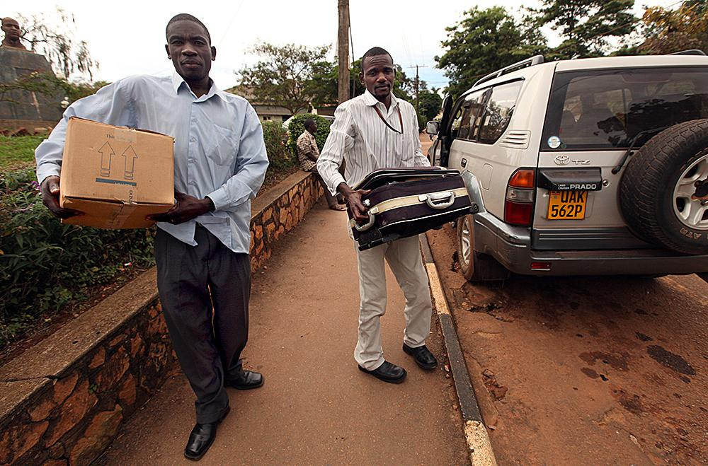 """<span class=""""photo-caption"""">Not all patients are well enough to come in for treatment. Each week, staff members head out into the streets of Kampala to reach patients who would not otherwise receive treatment. Chaplain Samuel Mahulu, left, and nurse Jude Mwaita, part of a home care team, carry supplies from their vehicle during one of their home care days.</span><span class=""""photo-credit"""">MCC Photo/Silas Crews</span>"""
