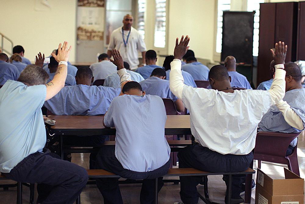 """<span class=""""photo-caption"""">Muse encourages the inmates through prayer at the end of the Bible study.</span><span class=""""photo-credit"""">MCC Photo/Silas Crews</span>"""