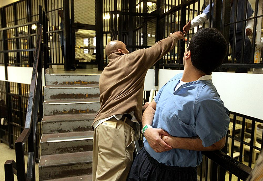 """<span class=""""photo-caption"""">Muse greets an inmate in a cellblock while talking with Angel Correa, right, who is Muse's childhood friend. Muse keeps in touch with Correa's family to make sure they are doing well.</span><span class=""""photo-credit"""">MCC Photo/Silas Crews</span>"""