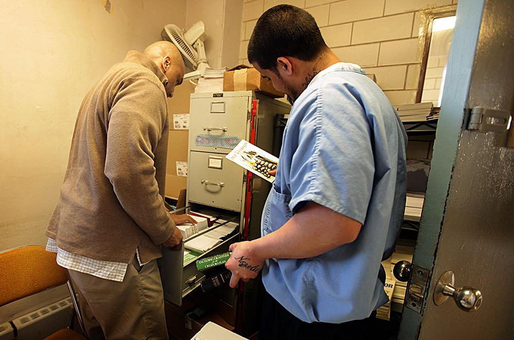 """<span class=""""photo-caption"""">An inmate looks through some of the resources Muse offers. Muse also makes the materials available at a Bible study he leads.</span><span class=""""photo-credit"""">MCC Photo/Silas Crews</span>"""