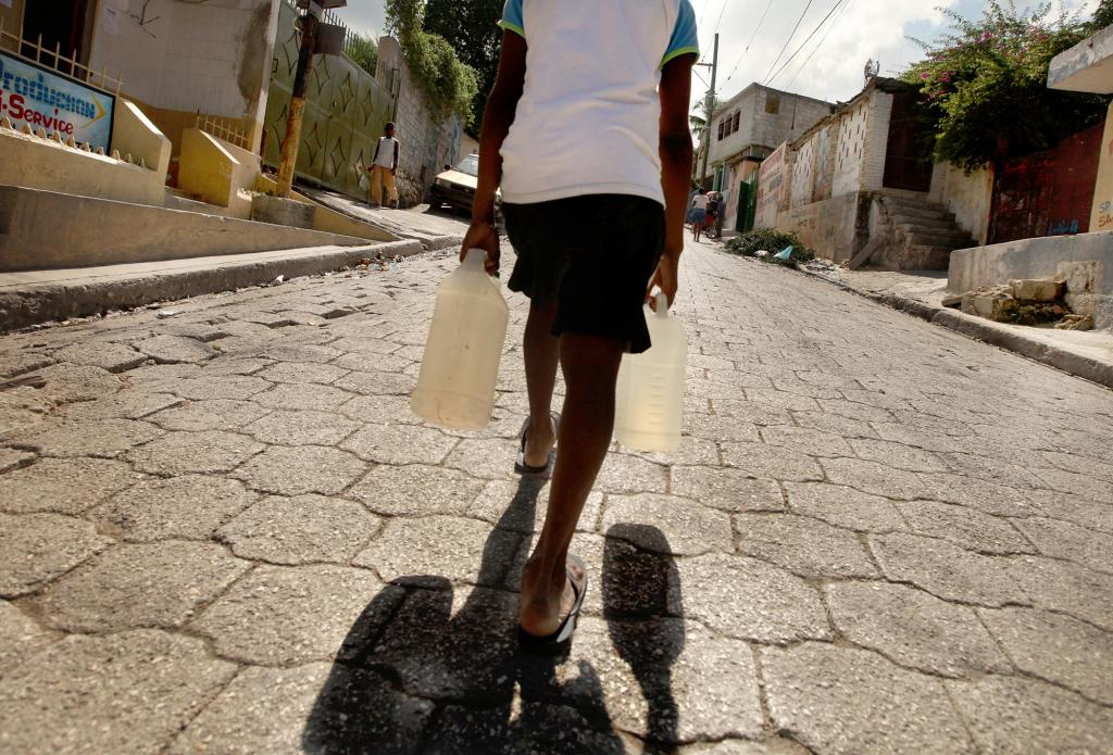 """<span class=""""photo-caption"""">Life in Haiti after the devastating Jan. 12, 2010, earthquake has been particularly hard for many of the nearly 300,000 unpaid child workers in Haiti who cook, fetch water and do other household chores. A child carries jugs of water near a school, run by MCC partner Ecumenical Foundation for Peace and Justice (FOPJ), that offers morning and afternoon sessions to children who spend the other parts of their day working.</span><span class=""""photo-credit"""">MCC Photo/Silas Crews</span>"""