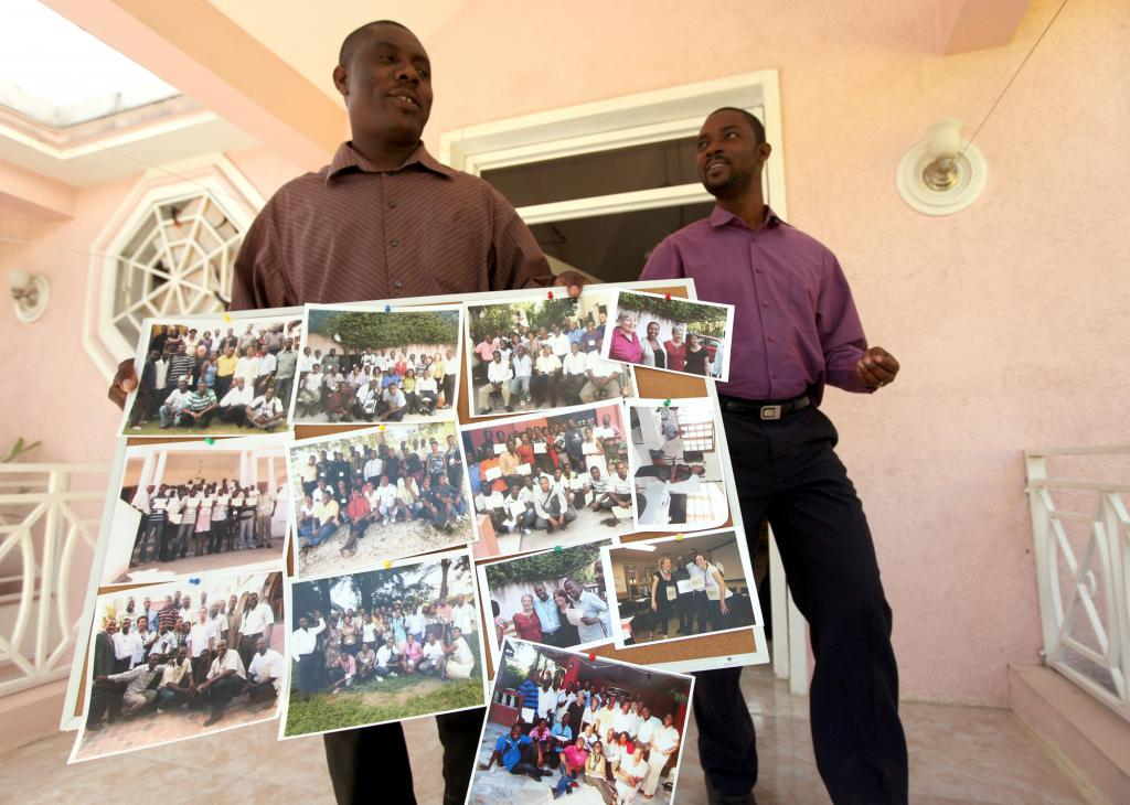 """<span class=""""photo-caption"""">Michel Garly, left, executive director of Wozo, and Harry Thelusma, Wozo program officer, hold a collection of group photos of trauma healing workshop participants. MCC provides support to Wozo, which holds trauma healing trainings around the country, working with those suffering from the earthquake and other needs.</span><span class=""""photo-credit"""">MCC Photo/Silas Crews</span>"""