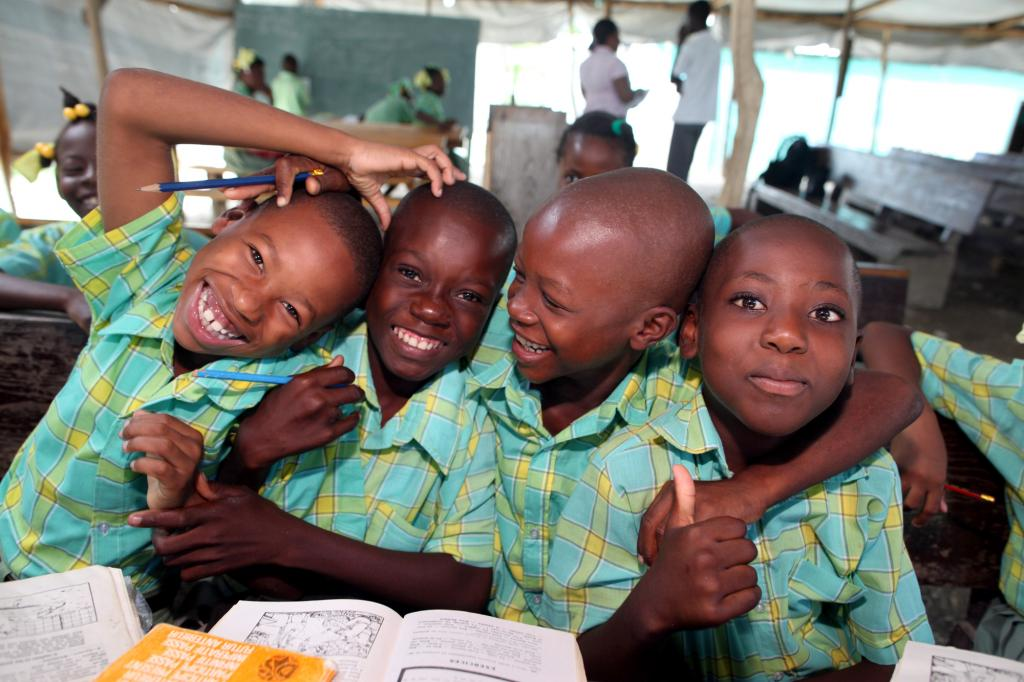 """<span class=""""photo-caption"""">Students pose for a picture during class, which takes place under tarps at Institution Chretienne de la Grâce, a school of Assemblée de la Grâce, a network of 23 Anabaptist congregations. The school building in Croix-des-Bouquets, Haiti, collapsed during the 2010 earthquake. MCC is supporting the construction of three classrooms.</span><span class=""""photo-credit"""">MCC Photo/Ben Depp</span>"""