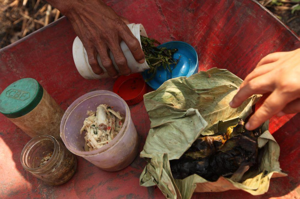 """<span class=""""photo-caption"""">Fish dishes, such as the one in the pink container, and rodents cooked in banana leaves provide valuable protein, while greens offer other important nutrients. Read more about thenutrition trainingsor about work tohelp families grow more ricein MCC's magazine, A Common Place.</span><span class=""""photo-credit"""">MCC Photo/Silas Crews</span>"""