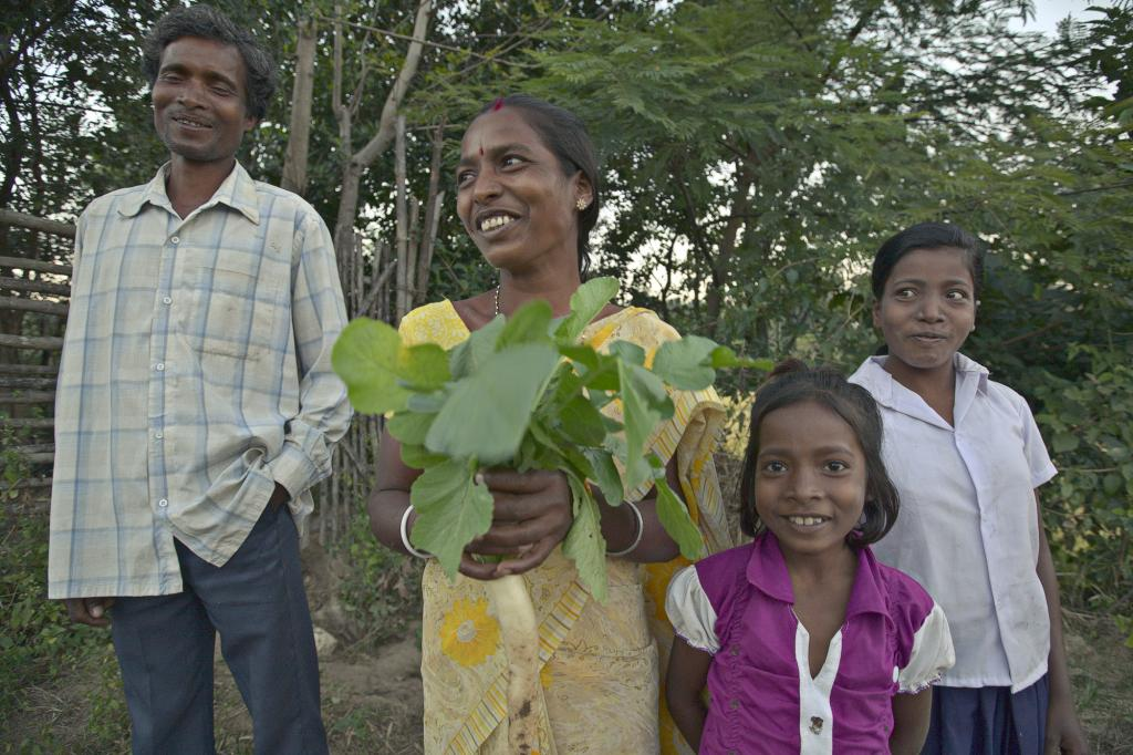 """<span class=""""photo-caption"""">In the Ranchi district of India's Jharkhand state, Hira Mani Sanga (with husband Sunil Sanga, and daughters Sumitra, 7, and Nirmala, 14) holds radishes that she and her family grew on their land. Sanga and her family are part of an MCC-supported project of South Vihar Welfare Society for Tribals (SVWST) that includes training in kitchen gardens, horticulture and animal husbandry.</span><span class=""""photo-credit"""">Melissa Hess</span>"""
