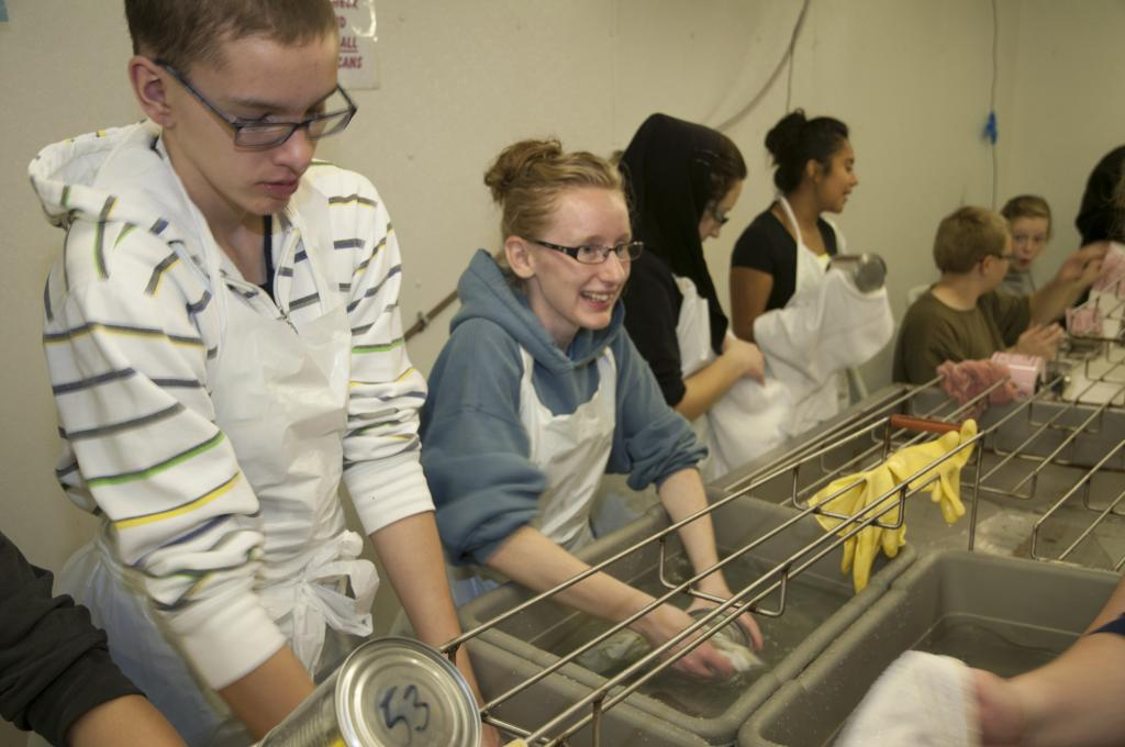 "<span class=""photo-caption"">Step 7: The freshly cooked and cooled cans are individually hand-washed and dried off by volunteers. </span><span class=""photo-credit"">MCC photo/Anthony J. Siemens</span>"