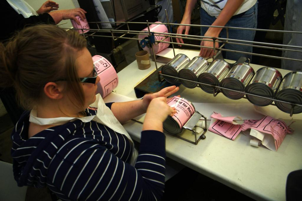 "<span class=""photo-caption"">Step 8: Volunteers apply a label to the finished cans indicating what kind of meat is inside. </span><span class=""photo-credit"">MCC photo/Anthony J. Siemens</span>"