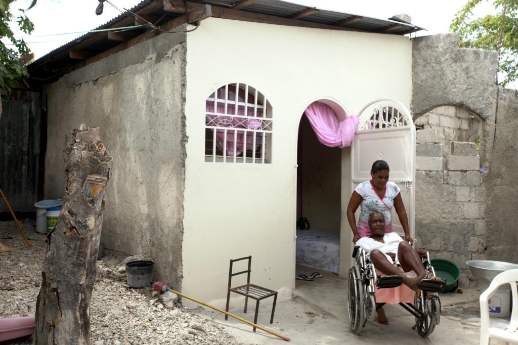 """<span class=""""photo-caption"""">Marie Antoinette Créa Exumé and daughter Nancy Marc not only had their roof replaced and new plaster put on through this project of MCC, Church World Service and Haitian partners Christian Center for Integrated Development and Service Chretien d'Haiti. They also got a wheelchair ramp. Today Marc can move her mother in or out of the house on her own. """"It changes everything,"""" Exumé says. """"Now I'm able to go out. When it's really hot inside, I can go outside.""""</span><span class=""""photo-credit"""">Silas Crews</span>"""