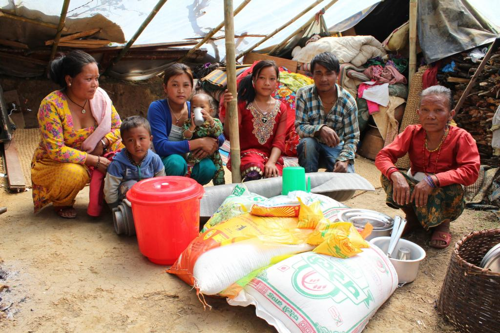 "<span class=""photo-caption"">Lama (right) and her family received relief materials from MCC, distributed through our Nepalese partner the Rural Institution of Community Development (RIOCD). Before getting sleeping mats from MCC, they were sleeping on a plastic sheet on the ground. They were only able to retrieve a small amount of their stored rice and other food from their kitchen. MCC also provided the family with three weeks of food (rice, lentils and oil). </span><span class=""photo-credit"">MCC photo/Binod Deshar</span>"