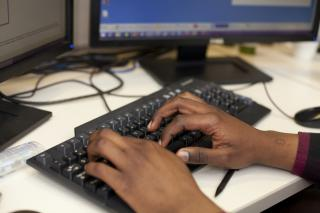 Hands on a keyboard in an MCC office