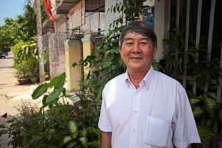 A man stands outside a building surrounded by plants.