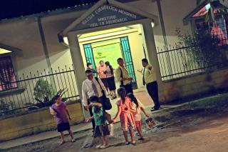 A group of children and adults stand outside a church highlighted by street and outdoor lights.