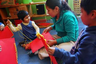 A smiling child sews fabric squares with a older child.
