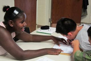 Rachel Stoltzfus helps participants sign in for their cooking class at Historic Roosevelt Summer Academy in Elkhart, Ind. Stoltzfus served as the academy's assistant coordinator in May, June and July through MCC U.S.' Summer Service program.