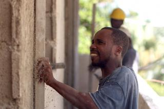 Former masonry student Ronald Sadou Zami, 25, smoothes a coat of mortar at a construction site where he works in Port-au-Prince, Haiti. Zami has been working for a month after graduating from a masonry professional program at MCC partner Ecumenical Foundation for Peace and Justice. He also attended a hazard reduction engineering seminar sponsored by MCC as part of its ongoing earthquake relief.