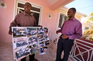 Holding group photos of many people trained in trauma healing, Michel Garly, left, executive director of Wozo, and Harry Thelusma, Wozo program officer, are excited that these people will teach others leaders and offer emotional help to those who suffered trauma from the earthquake. Wozo is an MCC partner that teaches healing techniques for those suffering trauma from the earthquake and other events.