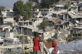 People view their collapsed homes in Nerettes, a neighborhood on the edge of Port-au-Prince, Haiti.