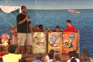 "Chris Collier or ""Captain Chris"" uses his high energy to engage the Vacation Bible School children at Living Water Community Church in Chicago. As part of MCC U.S.' Summer Service Worker program, Collier planned and led the three-week VBS based on the theme of ""High Seas Expedition."""