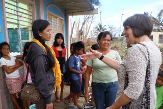 Jeanne Jantzi, right, talks with teachers Janett Yubal, left, and Selvia Luna, center, about their experience with Typhoon Haiyan, which devastated parts of the Philippines in early November. Community members took shelter in the Dalinding village elementary school on the island of Cebu, until the winds blew away large swaths of roof. Jantzi, Mennonite Central Committee's (MCC) Southeast Asia area director with her husband, Dan Jantzi, visited the school to assess ongoing ways that MCC can respond to the di