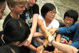 Teens living in China, Japan, and Korea build group cohesiveness at the first northeast Asia peace camp through this exercise of joining hands and then untangling themselves.
