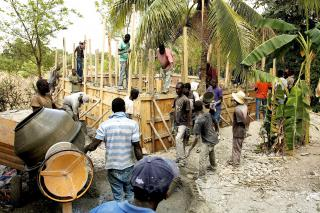 Haitian workers build a new reservoir to hold water from one of the three mountain springs that provides water to the town of Desarmes. Water from the reservoir will flow into pipes that will deliver reliable, drinkable water to households and public kiosks in the area. (MCC Photo/Josh Steckley)