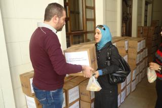 In Damascus, a woman accepts a box of food supplied by MCC through its partner, the Syrian Orthodox Church. People in the photo are not identified for security reasons. (Photo courtesy of the Syrian Orthodox Church) (Photo courtesy of the Syrian Orthodox Church)
