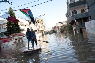 A week after torrential rains caused floodwaters to reach about 12 feet, Palestinians use fishing boats to assist residents in retrieving belongings from homes along flooded streets in the Al Nafaq section of Gaza City, Dec. 18. (MCC Photo/Ryan Rodrick Beiler)