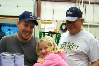 Mark Schroeder (left), his daughter Brin and his father Arlyss, seen here in 2009, regularly help with MCC's meat canning when it comes to North Newton, Kan.