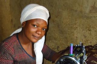 "Faith Alive graduate Anna Ayuba uses her MCC-funded sewing machine in Jenta – a neighborhood of closely built homes and dirt roads – where her earnings provide much needed assistance to her family. ""My parents are very happy. I am even sewing for the family now."""
