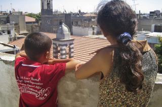 In a more peaceful time, orphans Alla and Marah look out over the city of Homs, Syria. Their orphanage, supported by MCC's Global Family education sponsorship program, has now moved to a safer location.