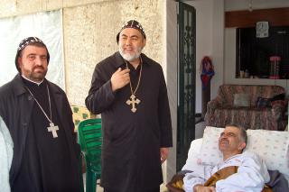 In April, Bishops Selwanos Petros al-Nemeh and Eustathius Matta Roham of the Syrian Orthodox Church, visited many people affected by violence in Homs, Syria, including Zaher Bakhos, a man who was shot and paralyzed by an unknown sniper.
