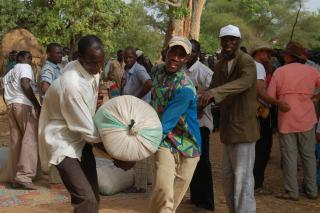 Two men carry a bag of millet at an MCC-supported food distribution in southwest Niger. Names are withheld for security reasons.