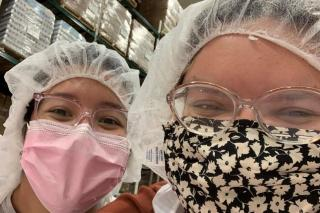 Two young women wearing hair nets in a warehouse